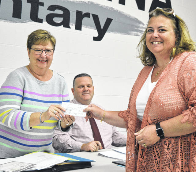 East Clinton Local Schools Board of Education President Linda Compton, left, accepts a $6,000 check from a representative of the East Clinton Athletic Boosters. Pictured also is Supt. Eric Magee, center.