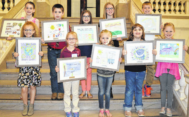 The winning artwork from the 2019 Earth Day poster contest — plus the young artists — were publicly congratulated Tuesday evening at the Clinton County Courthouse. The event and contest are held annually by the Clinton County Solid Waste Management District. From left in the front row are Alysse Stewart (Wilmington Christian Academy third-grader), Olivia Massie (Wilmington Christian Academy kindergartner), Kaylynn Hayslip (Holmes Elementary kindergartner), Audrey Pence (Clinton-Massie Elementary first-grader), and Bella Mahanes (New Vienna Elementary first-grader); and from left in the back row are Ashlynn Littrell (Wilmington Christian Academy fourth-grader), Max Carmack ((Holmes Elementary second-grader), Kameron Ward (Blanchester Intermediate fifth-grader), Riley Blom (Clinton-Massie Elementary fifth-grader), and Branson Taylor (Putman Elementary third-grader).