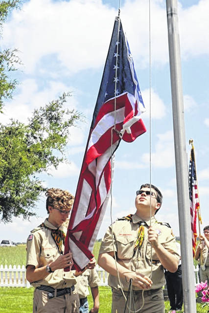 Boy Scouts raise the flag Monday afternoon, Memorial Day, at the Garrison Cemetery on Shawnee Trace Road in Clinton County.