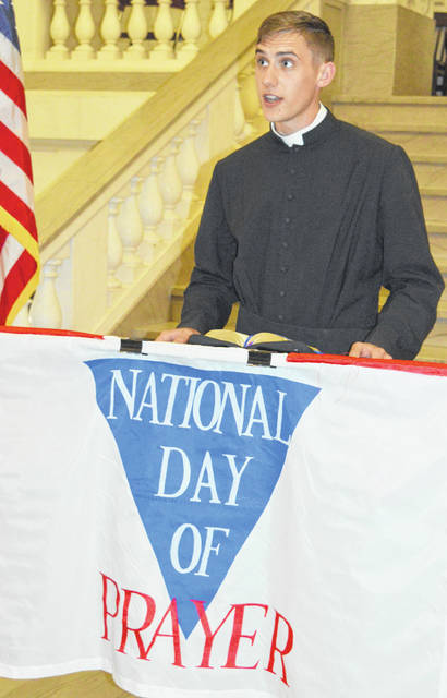 Seminarian Eddie Hoffman with the St. Columbkille Catholic Church in Wilmington reads from the Bible before saying a prayer at the local observance of the National Day of Prayer. Hoffman's internship at the local church will end this month, and then he will become a chaplain in the armed forces. The prayer event was held in the county courthouse.