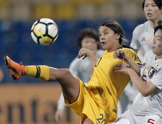 FILE - In this April 20, 2018, file photo, Australia's Samantha Kerr, left, fights for control of the ball against Japan's Nana Ichise , bottom right, during the AFC Jordan 2018 Women's Asian Cup final in Amman, Jordan. The Women's World Cup kicks off Friday, June 7, 2019, in Paris. Twenty-four teams will traverse France for the next month in pursuit of soccer's most prestigious trophy. (AP Photo/Raad Adayleh, File)