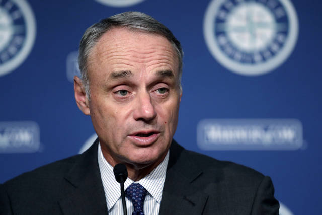 Baseball Commissioner Rob Manfred addresses reporters before a baseball game between the Seattle Mariners and the Houston Astros on Tuesday, June 4, 2019, in Seattle. (AP Photo/Elaine Thompson)