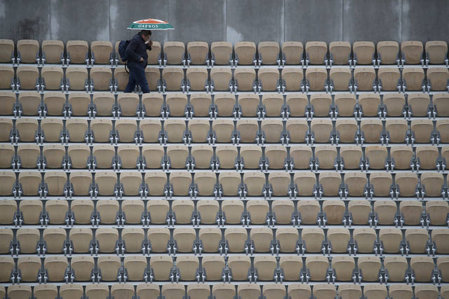 A spectator with an umbrella walks away after all matches of the French Open tennis tournament were cancelled due to rain at the Roland Garros stadium in Paris, Wednesday, June 5, 2019. (AP Photo/Christophe Ena)
