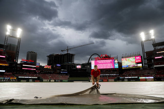 Busch Stadium grounds crew member Lucas Hackmann helps pull a tarp over the field just prior to the scheduled start of a baseball game between the St. Louis Cardinals and the Cincinnati Reds on Wednesday, June 5, 2019, in St. Louis. (AP Photo/Jeff Roberson)
