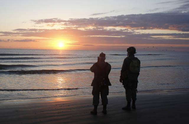 World War II reenactors stand looking out to sea on Omaha Beach, in Normandy, France, at dawn on Thursday, June 6, 2019 during commemorations of the 75th anniversary of D-Day. (AP Photo/Thibault Camus)