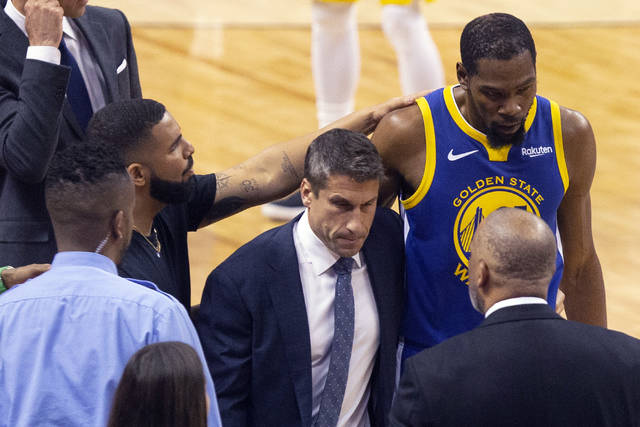 Golden State Warriors forward Kevin Durant, right, is consoled by Drake as he walks off the court after sustaining an injury during first half basketball action in Game 5 of the NBA Finals against Toronto Raptors in Toronto, Monday, June 10, 2019. (Chris Young/The Canadian Press via AP)