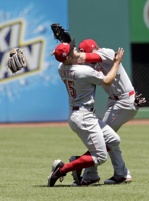 Cincinnati Reds' Nick Senzel, left, and Jose Peraza collide going after a ball hit by Cleveland Indians' Francisco Lindor in the first inning in a baseball game, Wednesday, June 12, 2019, in Cleveland. Senzel caught the ball and Lindor was out on the play. (AP Photo/Tony Dejak)