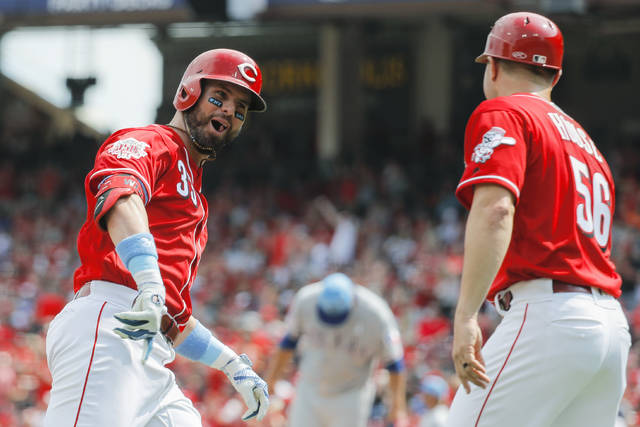Cincinnati Reds' Jesse Winker, left, celebrates as he runs the bases after hitting a two-run home run off Texas Rangers starting pitcher Ariel Jurado in the fourth inning of a baseball game, Sunday, June 16, 2019, in Cincinnati. (AP Photo/John Minchillo)