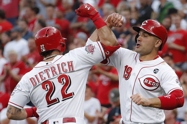 Cincinnati Reds' Derek Dietrich (22) celebrates with Joey Votto (19) after hitting a two-run home run off Houston Astros starting pitcher Justin Verlander during the first inning of a baseball game Tuesday, June 18, 2019, in Cincinnati. (AP Photo/John Minchillo)