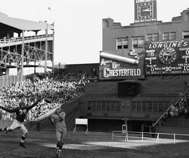 FILE - In this Nov. 14, 1948, file photo, Los Angeles Rams' Howard Hickey (53) catches a pass for a touchdown as New York Giants' Tony Minisi (38) defends at the Polo Grounds in New York.  In its early days, the NFL often relied on baseball stadiums for its teams. Often, the football team took the name of the baseball team, looking to create the illusion there was a connection between the teams. But once pro football expanded and was shown for free on television, the sport was on its way. (AP Photo/HH, File)