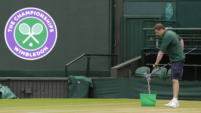 FILE - In this July 13, 2017, file photo, Ben Sidgwick wrings out his mop on Center Court at the All England Club at the Wimbledon Tennis Championships in London. Wimbledon was first played in 1877 and is the oldest Grand Slam tennis tournament. (AP Photo/Alastair Grant, File)