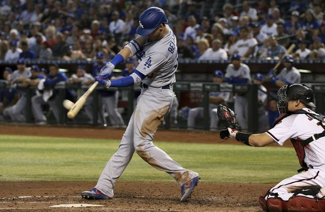 Los Angeles Dodgers' Cody Bellinger (35) connects for a home run as Arizona Diamondbacks catcher Caleb Joseph, right, reaches out for the baseball during the fourth inning of a baseball game Wednesday, June 26, 2019, in Phoenix. (AP Photo/Ross D. Franklin)