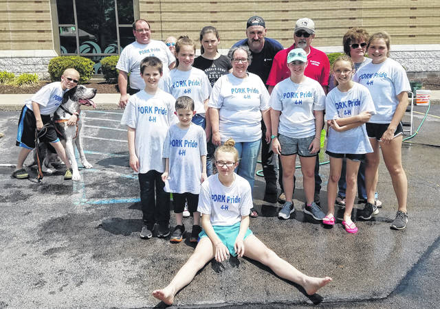 At the Pork Pride Car Wash on May 25 at Peoples Bank are: front, Mikala Hatfield; second row, Stanley and Isaac Chesney; third row, Gregary Achtermann, Mufasa, Cadence Setty, Judy Hatfield, Katie Pittman and Taylor Garringer; fourth row, Greg Achtermann, Peninah Latham, Randy Pinkerton and Jami Dailey; and back row, Kristina Achtermann, Terry Hatfield and Melinda Pinkerton. Not shown is Ebon Louderback.