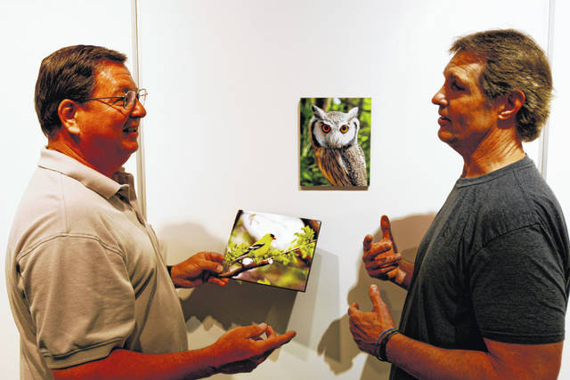 David Rupp, left, works with curator Hal Shunk in the placement of his nature photographs in WC's Harcum Gallery. Both men are presenting photographs in the exhibit.