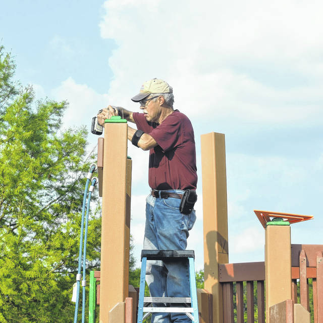 Former Clinton County Common Pleas Judge Allen Gano helps with constructing the new castle playground at David Williams Park on Saturday. Gano's wife, Judy, was a driving force behind the original castle park construction 25 years ago.
