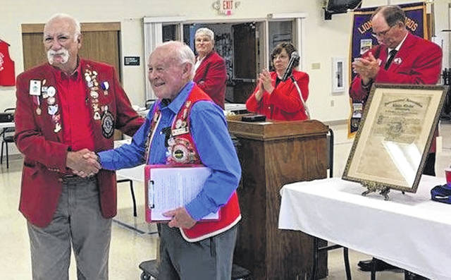 Past District Governor Gary De Fayette, left, presents Lion Joe Curtin with his 50-year Lions Service Pin.