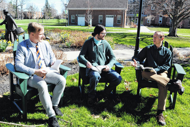 From left, Dr. Evan Farr, visiting assistant professor of humanities and global issues, junior Jack Ferguson and Dr. Stephen Potthoff, associate professor of religion and philosophy, enjoy a discussion against the backdrop of spring on campus.