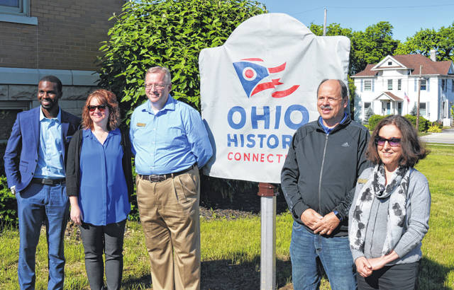 Prior to unveiling the state historical marker for the Wilmington Public Library, several people lined up for a photograph. From left are Ibrahima Sow with the Ohio History Connection, Ruth Brindle on behalf of the Wilmington-Clinton County Chamber of Commerce, Main Street Wilmington, and of the Ohio Local History Alliance, Library Director Joe Knueven, library board President Jeff Linkous and librarian Pam Ade, MLS.