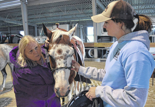 Jane Dickard of Dayton, left, gets acquainted with a horse before riding it. Trail M Boarding and Guest Farm staffer Liz Barrett, right, assists the sight-impaired Dickard, who is a member of the Alumni Association of Pilot Dogs group.