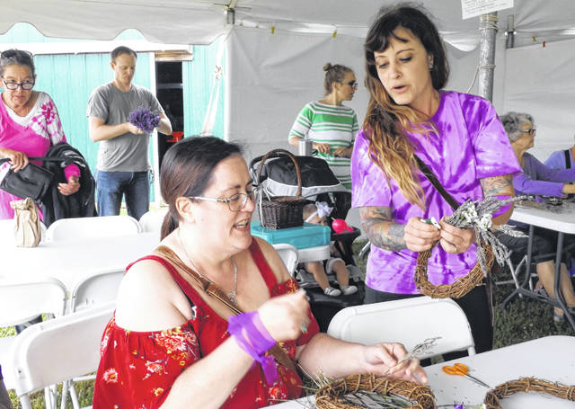 A lavender wreath workshop is a popular activity at the Summer Solstice Lavender Festival. In the foreground from left are Heather Crawford from Delaware, Ohio receiving instructions from Kym Prell of the Peaceful Acres Lavender Farm where the annual festival is held in Clinton County.