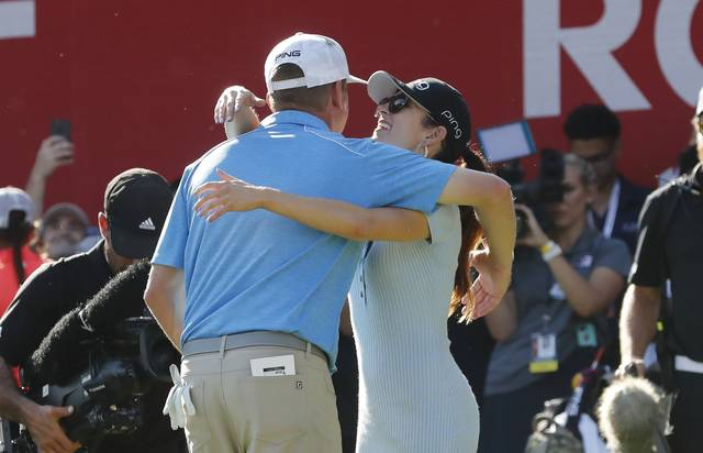 Nate Lashley, left, hugs his girlfriend Ashlie Reed on the 18th green after winning the Rocket Mortgage Classic golf tournament, Sunday, June 30, 2019, in Detroit. (AP Photo/Carlos Osorio)
