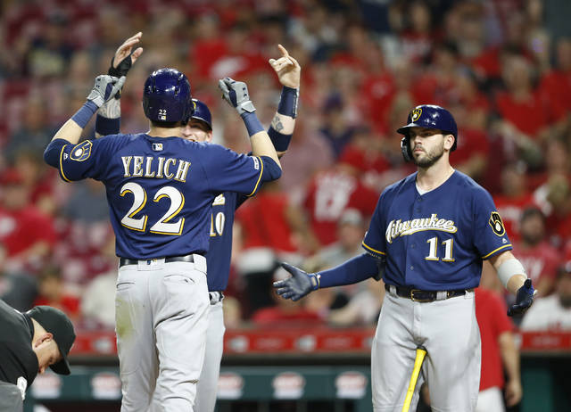 Milwaukee Brewers' Christian Yelich (22) is congratulated at the plate by Yasmani Grandal, obscured, left, and Mike Moustakas (11) following a two-run home run off Cincinnati Reds relief pitcher Robert Stephenson during the ninth inning of a baseball game, Monday, July 1, 2019, in Cincinnati. (AP Photo/Gary Landers)