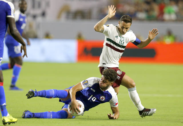 Haiti midfielder Steeven Saba and Mexico midfielder Andres Guardado (18) fight for the ball during the first half of a CONCACAF Gold Cup soccer match, Tuesday, July 2, 2019, in Glendale, Ariz. (AP Photo/Rick Scuteri)