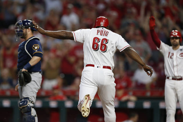 Cincinnati Reds' Yasiel Puig (66) scores on a single by Jose Iglesias (4) as Milwaukee Brewers catcher Manny Pina, left, looks for a throw during the seventh inning of a baseball game, Wednesday, July 3, 2019, in Cincinnati. (AP Photo/Gary Landers)