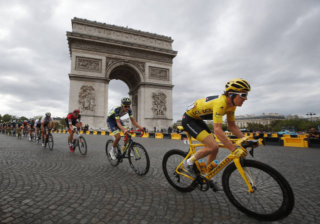 FILE - In this July 29, 2018 file photo, Tour de France winner Britain's Geraint Thomas, wearing the overall leader's yellow jersey, passes the Arc de Triomphe during the twenty-first stage of the Tour de France cycling race over 116 kilometers (72.1 miles) with start in Houilles and finish on Champs-Elysees avenue in Paris, France. Chris Froome's absence, coupled with the withdrawal of last year's runner-up Tom Dumoulin, has reshuffled the game and produced a long list of top contenders. (AP Photo/Christophe Ena, File)