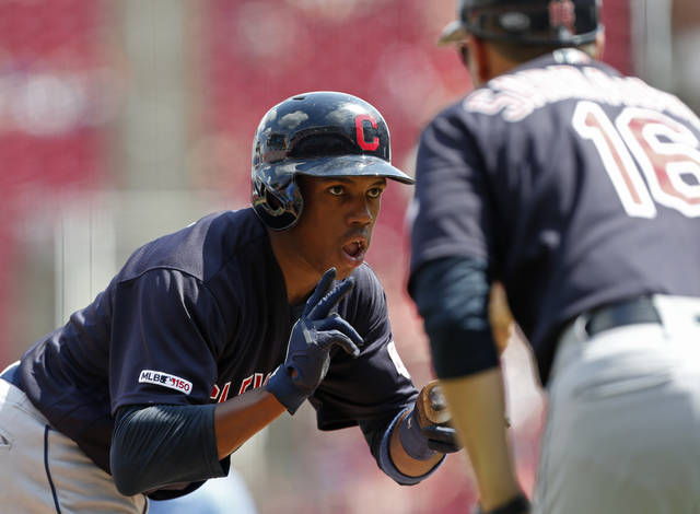 Cleveland Indians' Greg Allen, left, reacts to a triple off Cincinnati Reds relief pitcher Robert Stephenson with third base coach Mike Sarbaugh (16) during the seventh inning of a baseball game, Sunday, July 7, 2019, in Cincinnati. (AP Photo/Gary Landers)