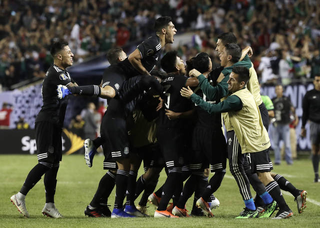 Mexico midfielder Jonathan Dos Santos (6) celebrates with teammates after scoring his first goal against the United States during the second half of the CONCACAF Gold Cup final soccer match in Chicago, Sunday, July 7, 2019. (AP Photo/Nam Y. Huh)