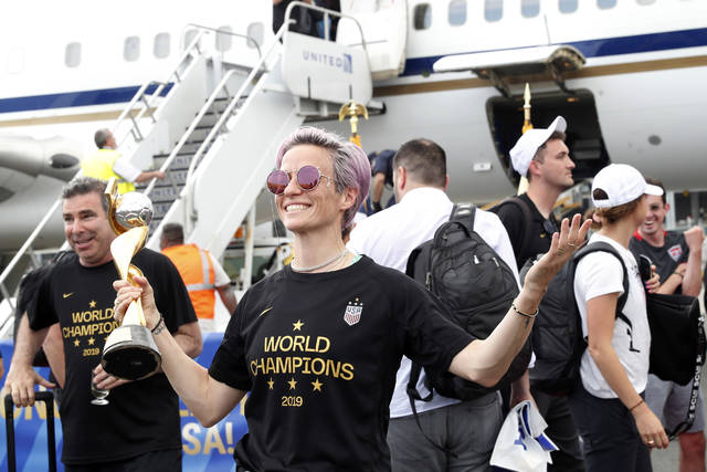 United States women's soccer team member Megan Rapinoe holds the Women's World Cup trophy after arriving with teammates at Newark Liberty International Airport, Monday, July 8, 2019, in Newark, N.J. (AP Photo/Kathy Willens)