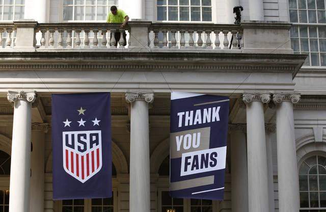 A worker hangs signs at City Hall one day ahead of a ticker-tape parade for the U.S. Women's World Cup winning team, Tuesday, July 9, 2019, in New York. (AP Photo/Kathy Willens)