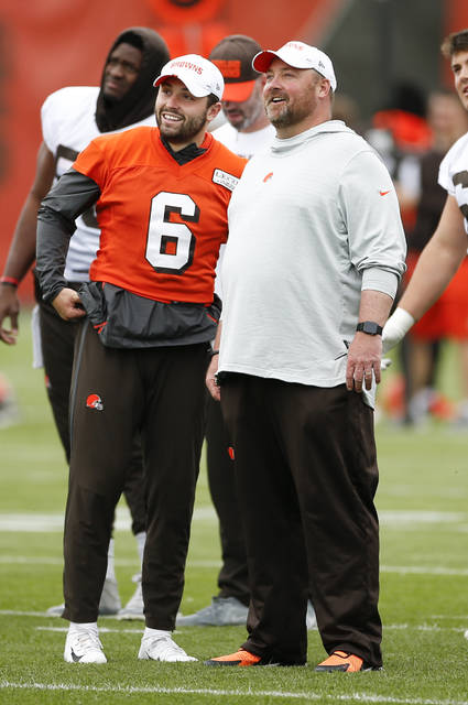 FILE - In this June 4, 2019, file photo, Cleveland Browns quarterback Baker Mayfield (6) talks with coach Freddie Kitchens at the team's NFL football training facility in Berea, Ohio. Of all the new hires, Kitchens might be under the most pressure considering the ramped-up expectations in Cleveland--and the potential for major disruptions. (AP Photo/Ron Schwane, File)