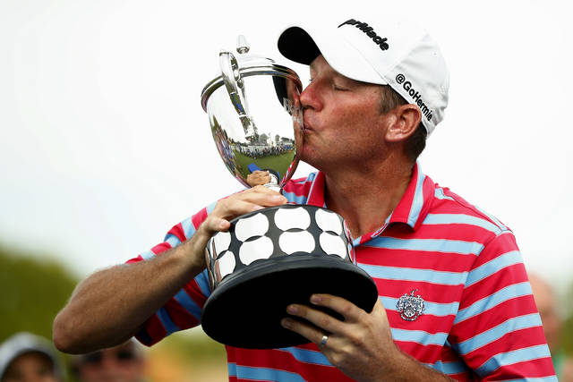 Jim Herman kisses the trophy after winning the PGA Barbasol Championship golf tournament at Keene Trace Golf Club's Champions Course in Nicholasville, Ky., Sunday, July 21, 2019. (Alex Slitz/Lexington Herald-Leader via AP)