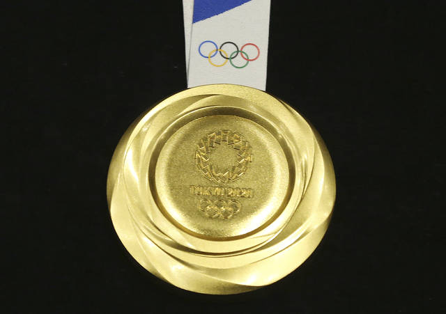 Tokyo 2020 Olympic gold medal is unveiled during a One Year to Go Olympic ceremony event in Tokyo Wednesday, July 24, 2019. Gold, silver, and bronze Olympic medals were to get their first public viewing on Wednesday as Tokyo organizers marked exactly a year until the games open. (AP Photo/Koji Sasahara)