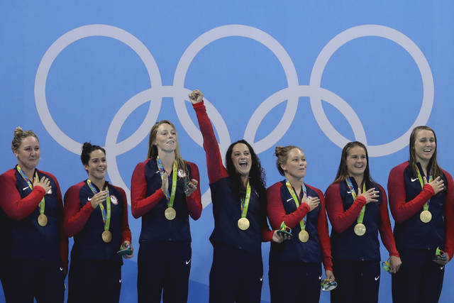 FILE - In this Aug. 19, 2016, file photo, members of the United States women's water polo team celebrate with their gold medals on the podium after winning their gold medal match against Italy at the 2016 Summer Olympics in Rio de Janeiro, Brazil. For decades, the question at the Summer Olympics hasn't been whether the United States will top the medals table, but by how much. If anyone on U.S. soil has a problem with that _ and given the headlines of the last few years, plenty of people do _ well, imagine the alternative. (AP Photo/Eduardo Verdugo, File)