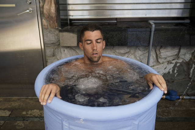 American beach volleyball player, Trevor Crabb, cools off in a bucket of ice water after competing during a test event at Shiokaze Park, a venue for beach volleyball at the Tokyo 2020 Olympics, Friday, July 26, 2019, in Tokyo. The heat is on for organizers of the 2020 Tokyo Olympics. Several days after marking one year to go before the opening ceremony, the notorious Tokyo heat kicked in just in time for a beach volleyball test event that gave organizers a chance to implement their heat countermeasures. (AP Photo/Jae C. Hong)