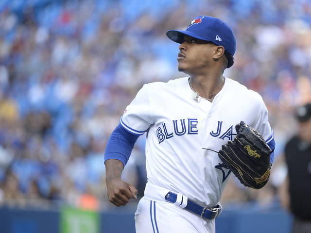 Toronto Blue Jays starting pitcher Marcus Stroman (6) looks back as a teammate makes a catch for an out against the Cleveland Indians during the first inning of a baseball game, Wednesday, July 24, 2019 in Toronto. (Nathan Denette/Canadian Press via AP)