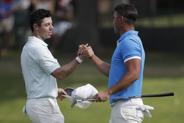 Rory McIlroy, of Northern Ireland, left, shakes hands Brooks Koepka after Koepka won the final round of the World Golf Championships-FedEx St. Jude Invitational, Sunday, July 28, 2019, in Memphis, Tenn. (AP Photo/Mark Humphrey)