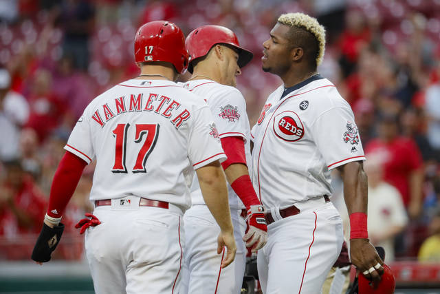 Cincinnati Reds' Jose Iglesias, center, celebrates with Josh VanMeter (17) and Yasiel Puig, right, after hitting a grand slam off Pittsburgh Pirates relief pitcher Montana DuRapau in the second inning of a baseball game, Monday, July 29, 2019, in Cincinnati. (AP Photo/John Minchillo)