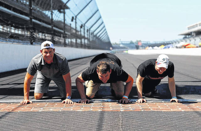 The winners kiss the bricks of the historic track.