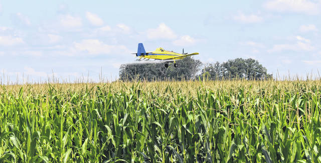 A plane sprays crops near Smith and Center Road in Clinton County this week.