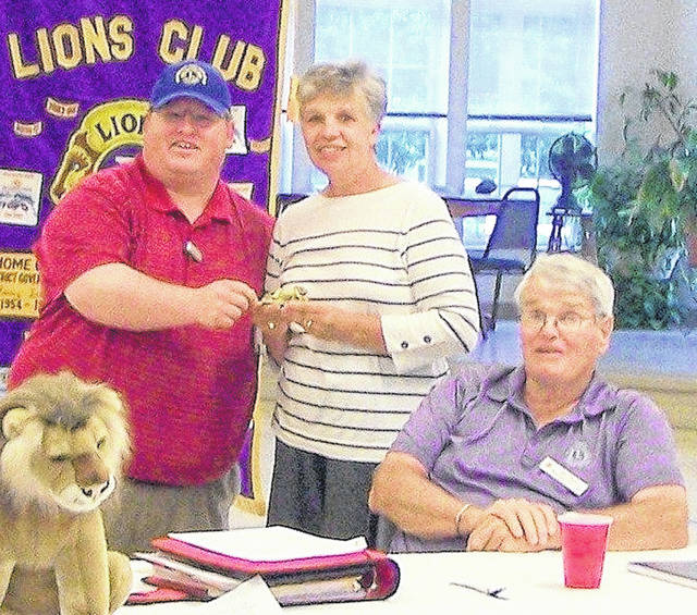 Lions Club President Ryan Page presents a lion statuette to Diane Murphy as Lion Nial Henry looks on.