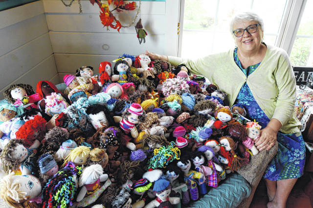 Nancy McCormick, Wilmington College's campus minister, sits with the 108 Japanese Friendship Dolls she will be taking to Japan in early August.