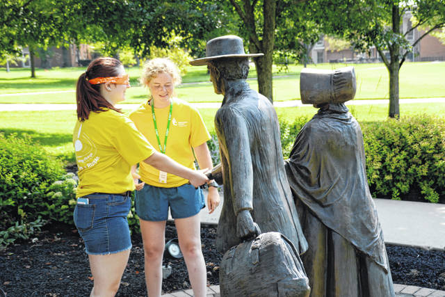 "Lauren Chafin, an incoming freshman from Stoutsville, guides a blindfolded Alex Gano, a new freshman from Wilmington, in an activity known as the ""Trust Walk,"" in which the Leadership Plunge participants are guided to various landmarks on campus. In this case, Alex shakes hands with Isaac Harvey at the Isaac and Sarah Harvey statue near the Quaker Heritage Center."