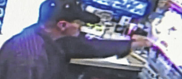 Screenshots of security footage of the armed suspect who robbed a Shell station on State Route 73 West on Saturday.