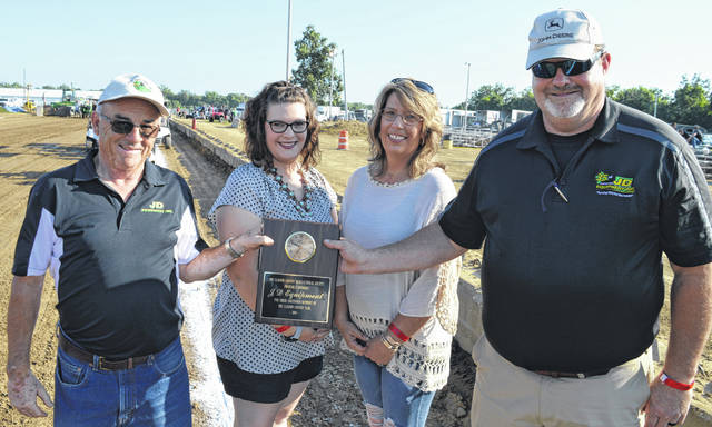 The Clinton County Agricultural Society Board of Directors (Fairboard) chose JD Equipment Inc. as the business to be recognized and honored at the 2019 county fair. The award recognizes a business that has positively affected the Ag Society, fairgrounds, and fair activities. Accepting on behalf of JD Equipment from left are Ed Smith, Kayla Alexander Jones, Melissa Gerber Alexander, and Tim Alexander. The Fairboard earlier during fair week recognized former Clinton County commissioner and former Clinton County sheriff Patrick Haley as the individual honoree for 2019.