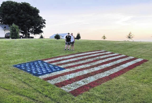Paige Younker, left, and Ashley Caplinger display the American flag they spray-painted in their New Vienna field for the Fourth of July.
