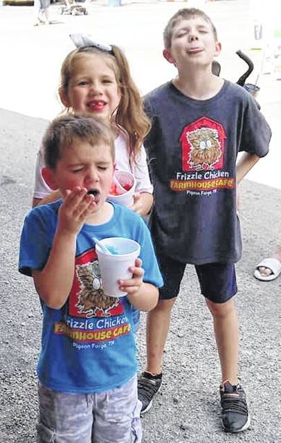 Kids cool off when they can and consume what they will as they enjoy a warm afternoon with their parents at the Clinton County Fair.